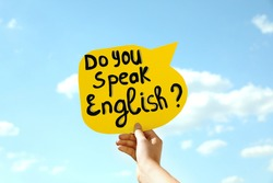 Woman holding paper speech bubble with question Do You Speak English against blue sky, closeup