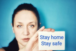 Woman holding paper with text message STAY HOME STAY SAFE on blue background. Coronavirus, COVID-19, self-quarantine, isolation, social disdancing concept.