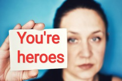 Woman holding paper with text message YOU'RE HEROES on blue background. Coronavirus COVID-19 pandemic.