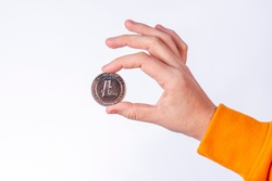 Woman holding physical Litecoin (LTC) coin. Cryptocurrency concepts on white background.