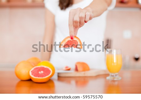 Woman holding piece of red grapefruit in the kitchen