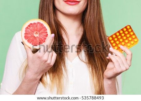 Woman holding pills blister pack vitamin c in one hand and grapefruit in another. Choice between natural and synthetic way of health care. Alternative medicine. Studio shot on green background #535788493