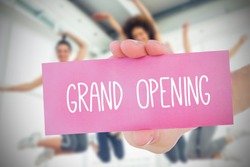 Woman holding pink card saying grand opening against class in gym