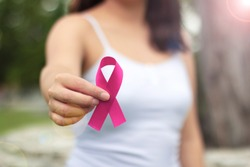 Woman holding pink ribbon on light background, closeup. Breast cancer awareness concept