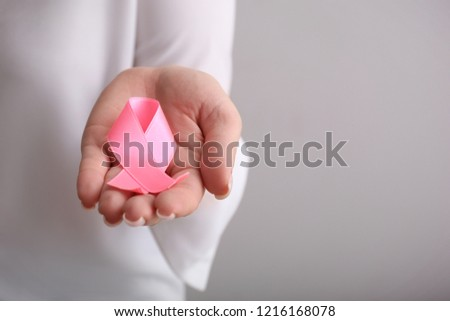 Woman holding pink ribbon on light background, closeup. Breast cancer awareness concept #1216168078
