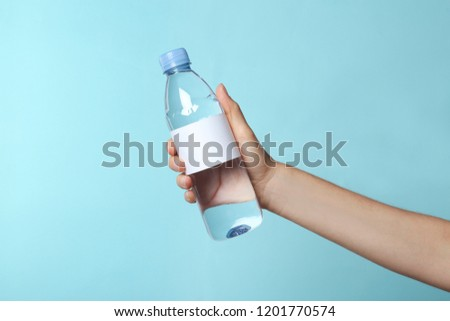 Woman holding plastic bottle of pure water with blank tag on color background
