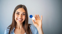Woman holding plastic container with contact lenses, indoors. Young woman holds case for contact lenses.  Woman holding contact eye lenses container