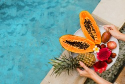 Woman holding plate of tasty  tropical exotic fruits  on the edge of pool, breakfast at luxury hotel. Slices of papaya, dragon fruit, passion fruit. Vegan and healthy food.