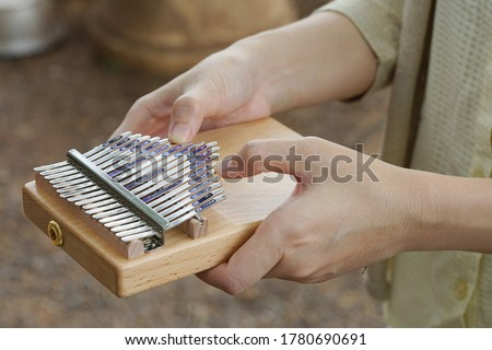Photo of  Woman holding play thumb piano or kalimba musical instrument.  play on hands and plucking the tines with the thumbs.