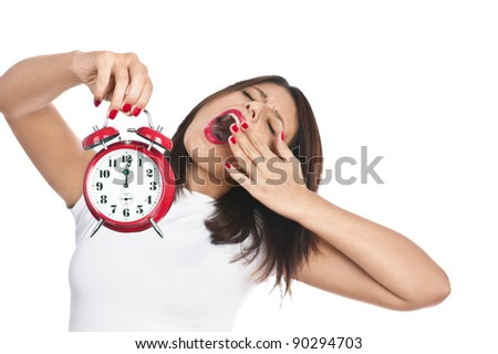 Woman holding red alarm clock yawning isolated on white. Focus is on clock.