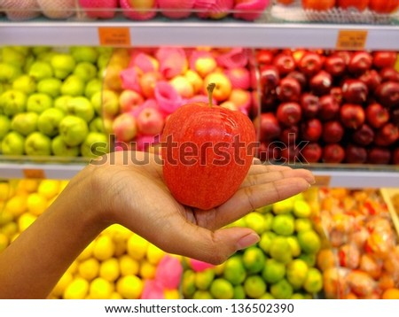 Woman holding red apple in supermarket with a background of lots of apples.