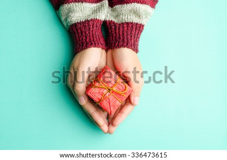 Woman holding red giftbox by hand on green background #336473615
