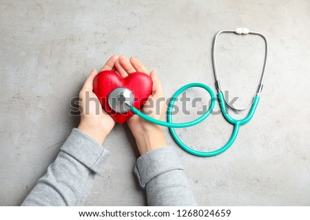 Woman holding red heart and stethoscope on gray background, top view. Cardiology concept Foto stock ©