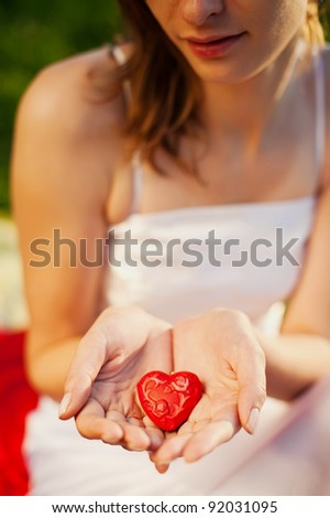 woman holding red heart in her hands - symbol of love