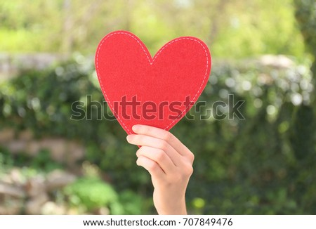 Woman holding red heart on blurred background. Volunteer concept #707849476
