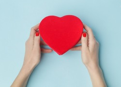 Woman holding red heart shaped box on the blue background. Valentine's day, mother's day, birthday, holiday concept.