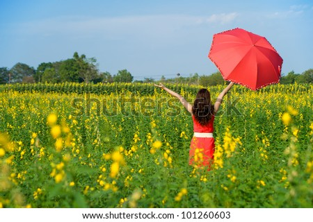 Woman holding red umbrella in Yellow flower field and cloud sky