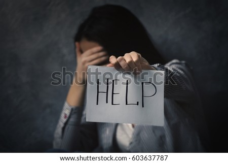 Woman holding sheet of paper with word HELP on grey wall background #603637787