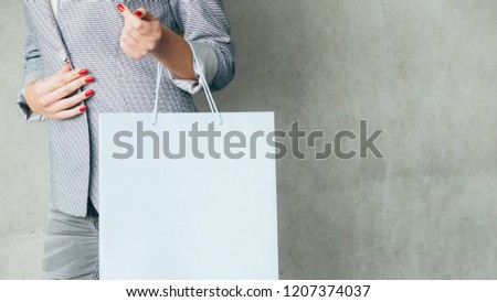 woman holding shopping bag. buying and consumerism concept. empty space for merchandise on white paper packet.