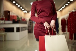 Woman holding shopping bags while standing on store front in the mall background. Consumerism concept. Copyspace on bag.