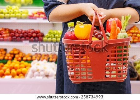 woman holding shopping basket in supermarket,fruit zone background