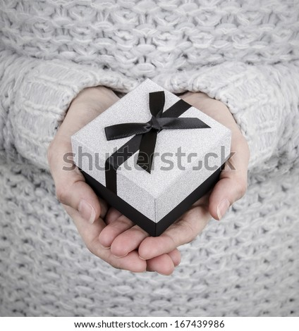 woman holding silver gift box with black ribbon