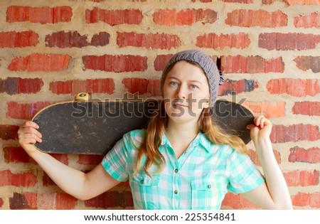 Woman holding skateboard against brick wall