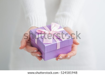 Woman holding small purple gift box in hands #524581948