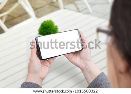 Woman holding smart phone in horizontal position. Isolated screen for mockup. White wooden desk and plant in background.