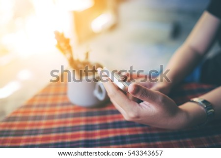 Woman holding smart phone on coffee table