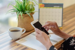 Woman holding smartphone to update calendar with notebook pencil diary vase on table with blurred calendar. planning scheduling agenda and event for 2018. Calendar and Planning concept.