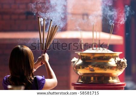 woman holding smoking big incense sticks in chinese temple, Kuala Lumpur, malaysia