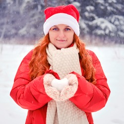 Woman holding snow in the shape of a heart in knitted mittens. Red-haired woman on Christmas and New Year Eve walks in the winter in red clothes