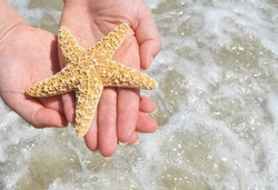 Woman holding starfish over surf
