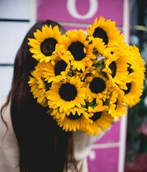 woman holding sunflowers at her back
