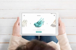 Woman holding tablet and use ecommerce app to find new shoes. Top view over the head.