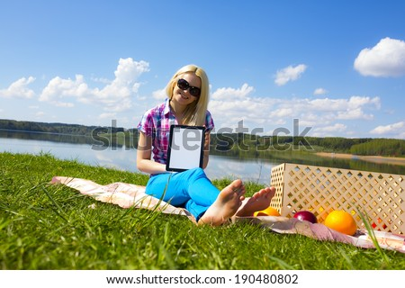 Woman holding tablet frame picnic