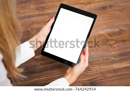 Woman holding tablet on wooden table.