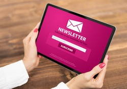 Woman holding tablet with newsletter signup page on screen