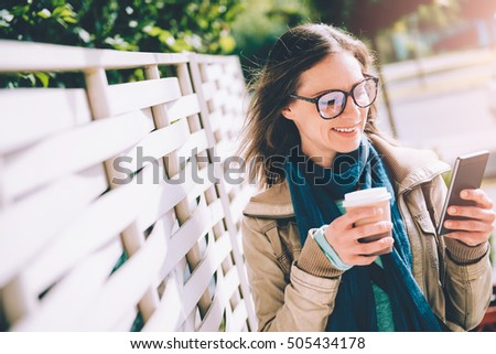Woman holding takeaway coffee and using smart phone outdoor #505434178