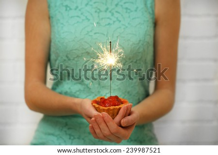 Woman holding tasty cake with sparkler, on grey wall background #239987521