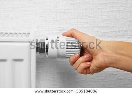 Woman holding temperature knob of heating radiator