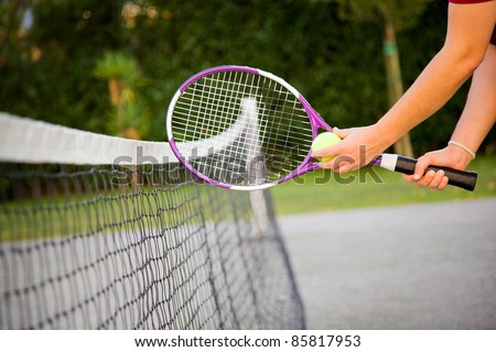 Woman holding tennis racket and ball close to the net