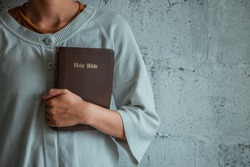 Woman holding the bible in the morning. copy space. Holy Bible in church concept.