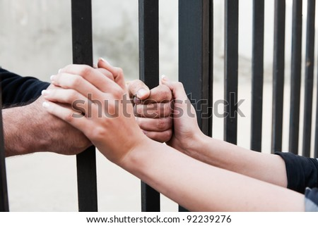 woman holding the hands of her husband behind the bars