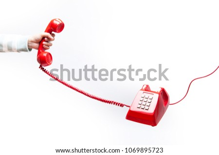 Woman holding the red phone, urgent call waiting , classic red telephone receiver in hand, old telephone isolated on white background flying in weightlessness.
