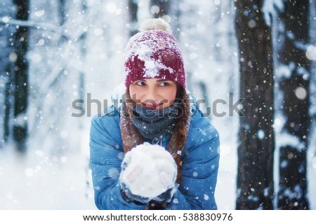 woman holding the snowball in hands. picture with soft focus. winter and people concept #538830976