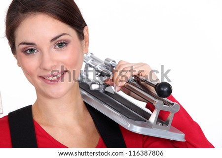 Woman holding tile cutting tool over shoulder - stock photo