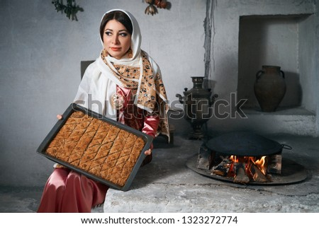 Woman holding tray with  baklava dessert, indoors. Novruz holiday celebration with beautiful azeri women in traditional Azerbaijani dress and national pastry pakhlava