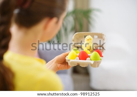 Woman holding tray with colorful Easter eggs and chicken
